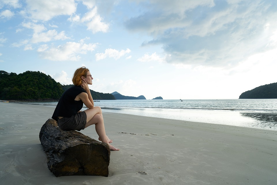 sad woman sitting on a log at the beach