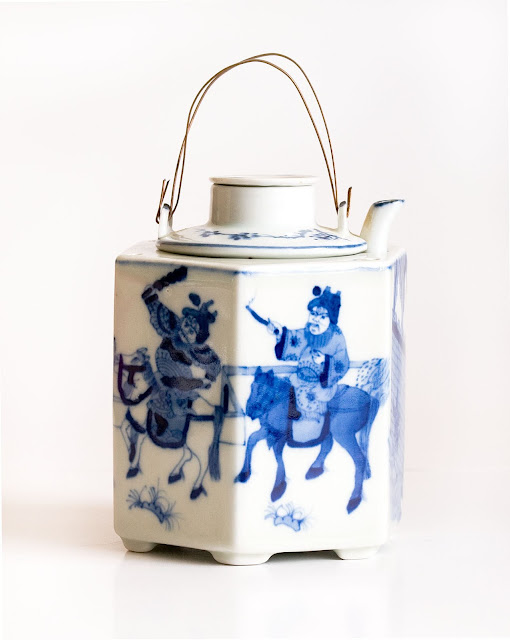 A Japanese teapot in blue and white design with horses and riders, and a wire handle.