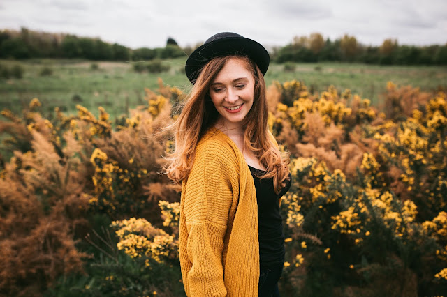 woman standing in front of yellow flowers in bowler hat and looking at the ground smiling