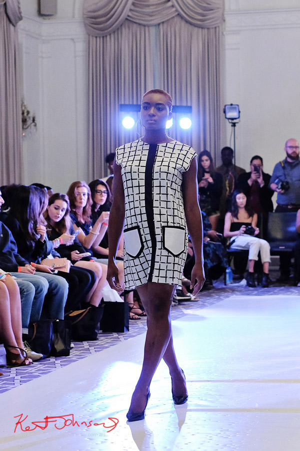 A model on the runway wearing a 60s inspired white and black windowpane check dress with patch pockets. André Bryson - Guerrilla - NYFW. Photographed for Street Fashion Sydney by Kent Johnson.