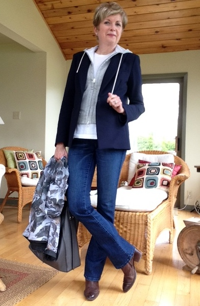 woman dressed in jeans, jacket and hoodie, holding a windbreaker and tote