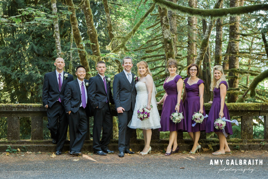 purple and white wedding party standing on road in the forest