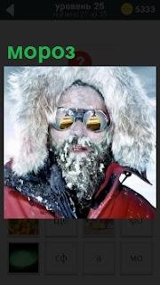 Мужчина в теплой куртке с капюшоном и очками с замерзшей бородой в сильный мороз