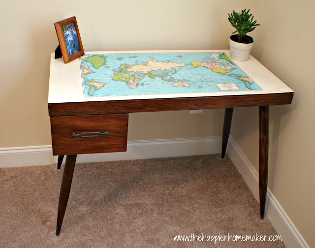 A map top wood desk with a picture frame and small plant on it