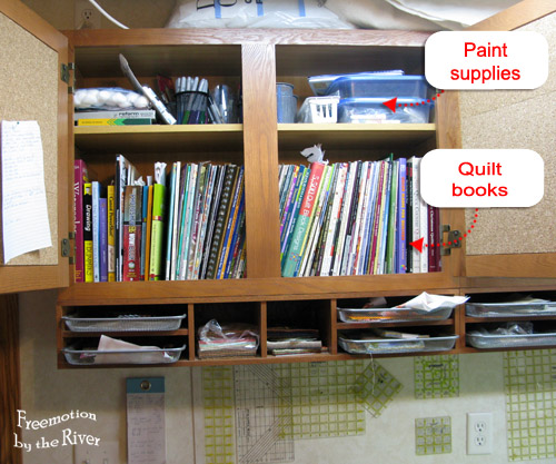 Quilt books and paints in cupboards