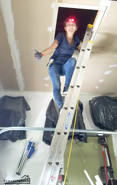 Cristina Garay up the ladder and ready to get in the attic space