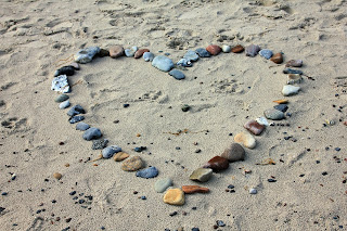 heart made out of many colored stones, on a sandy beach