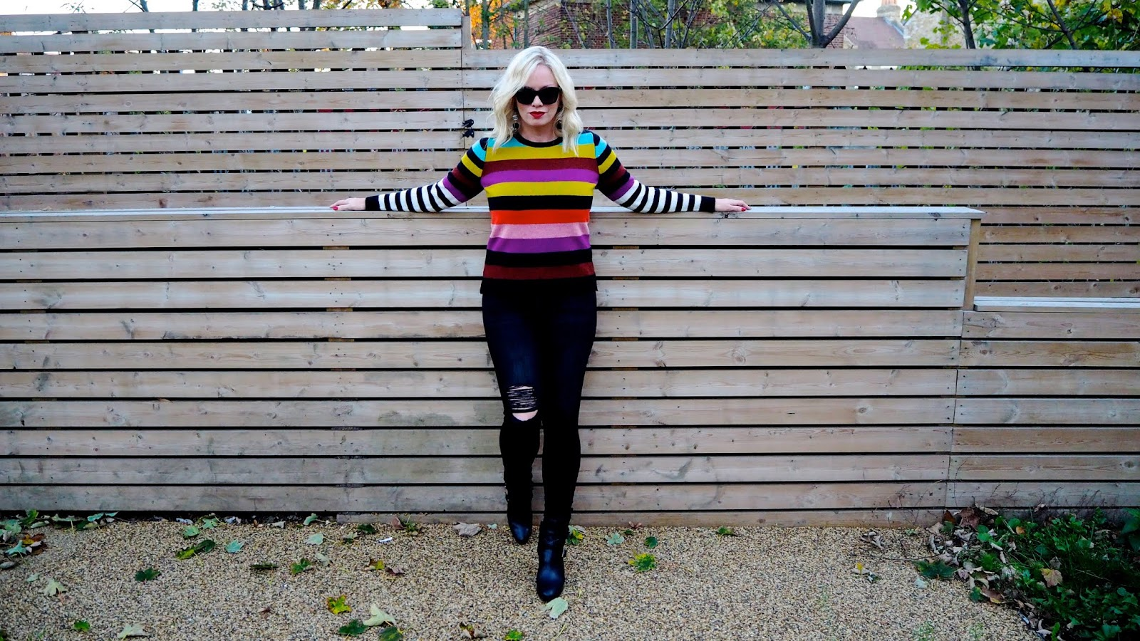 colourful, striped sweater and black ripped jeans standing in front of a wooden fence