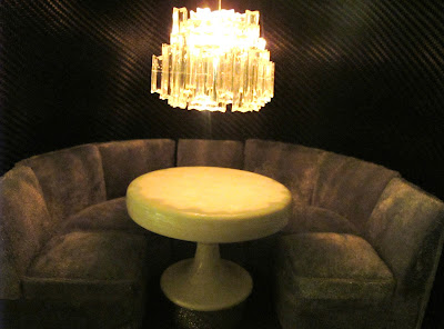 Modern dolls' house miniature circular booth, table and modern chandelier above.