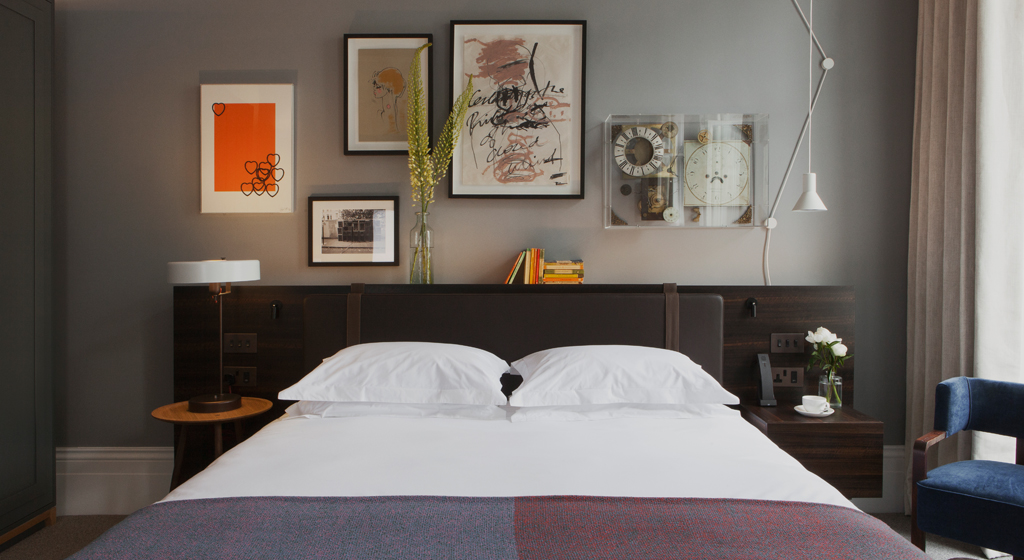 Guest room with art gallery wall over bed at Laslett Hotel in Notting Hill in the heart of West London
