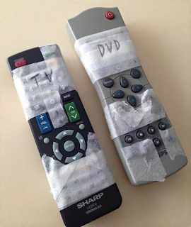 Labelled remotes with tape over certain buttons