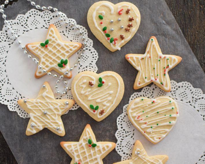 Galletas cortadas en forma de estrellas y corazón y decoradas con glaseado real y lluvia de colores