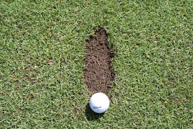 A Titleist golf ball placed behind a shallow divot, demonstrating the ideal spot for taking divots