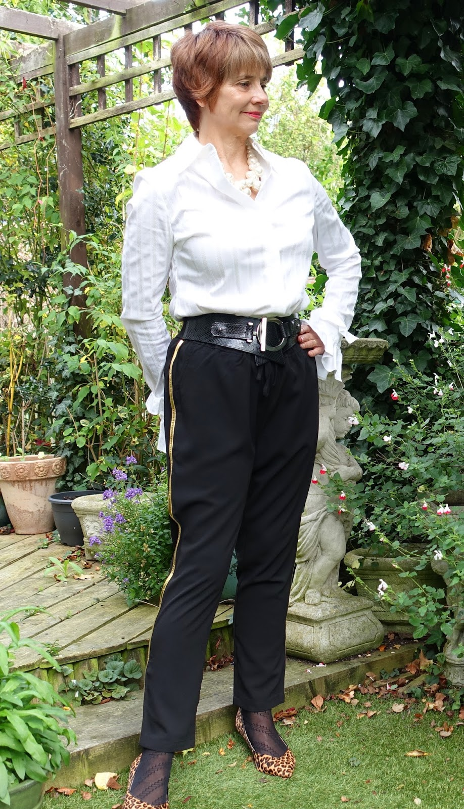 Image showing over 40s blogger Gail Hanlon from Is This Mutton in gold side striped trousers and Teatum Jones white shirt with leopard print kitten heels.