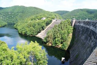 Eine Staumauer, umgeben von viel Wasser und Wald