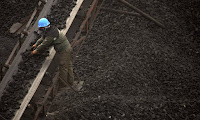 Worker adjusts coal in chute (Photograph Credit: Mark Schiefelbein/AP) Click to Enlarge.