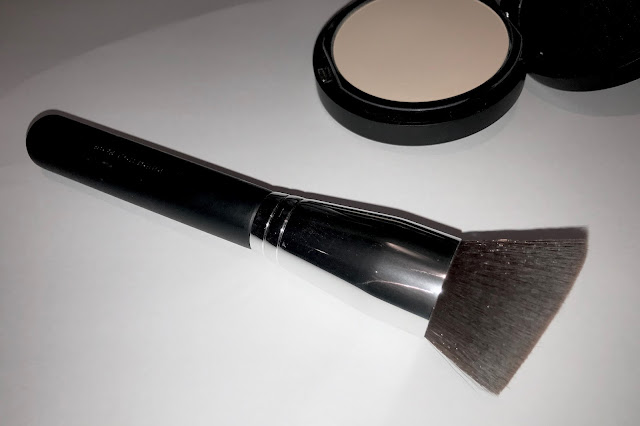 A close up of the make up brush with a black handle and silver metal  end holding in lots of dark, finely packed hairs