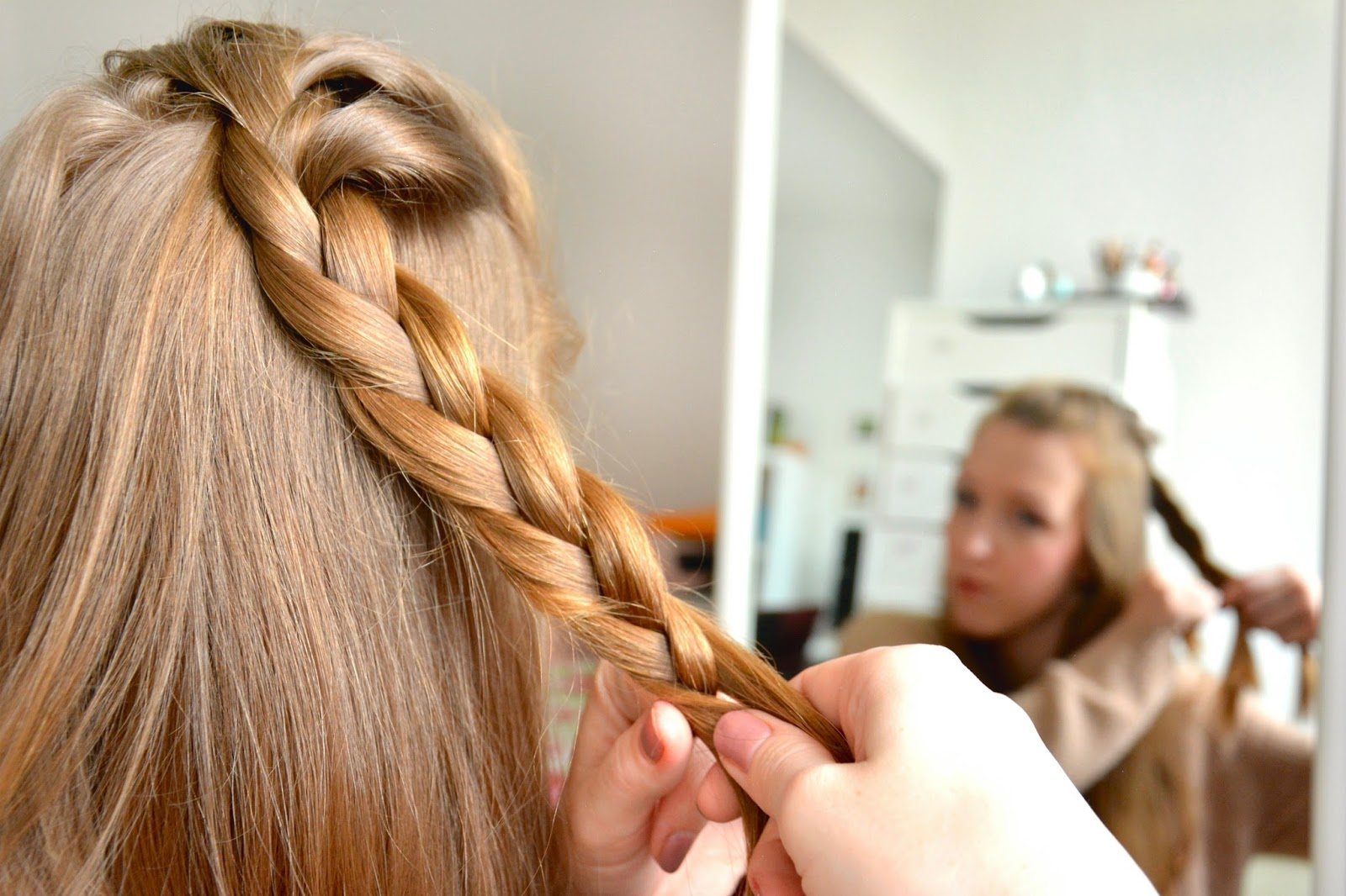 Girl in front of mirror; blonde hair; hair styling; braid
