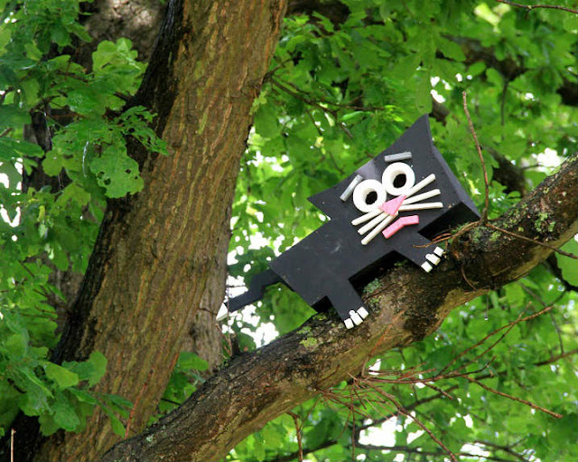 Wooden cat statue fitted on Trees