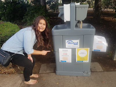 Ericka next to a handwashing station with notices about Hepatitis A