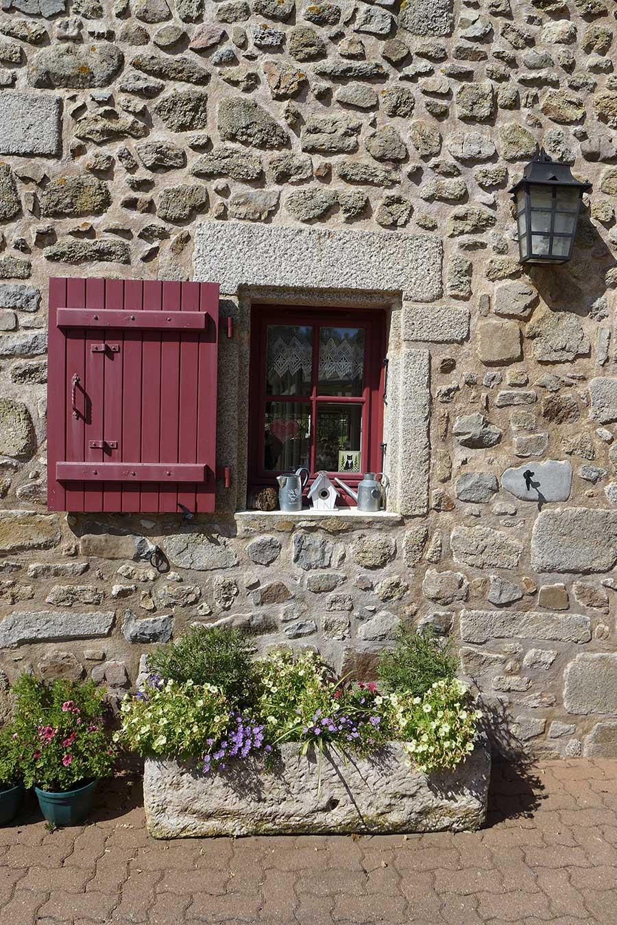 petite fenêtre rouge façade en pierre