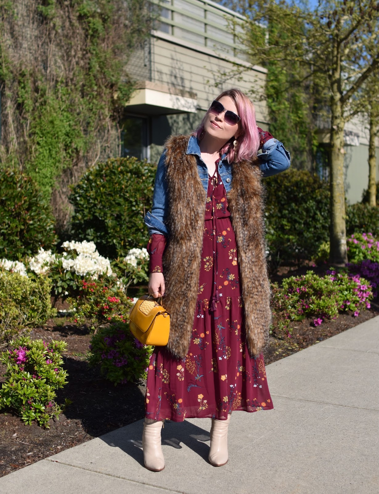Monika Faulkner outfit inspiration - styling a floral maxi dress with a denim jacket, long faux-fur vest, and ivory ankle boots