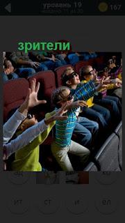в зале сидят дети в качестве зрителей протягивают руки в очках