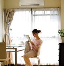 A woman reading at a table next to a ductless A/C vent