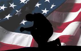 Pray for America:  Silhouette of a Man Kneeling in Prayer in front American Flag Waving in Breeze