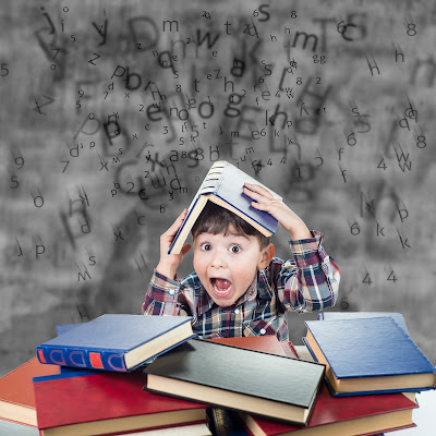 young boy with a blackboard with scattered alphabet surrounded by books holding a book over his head with animated stress face