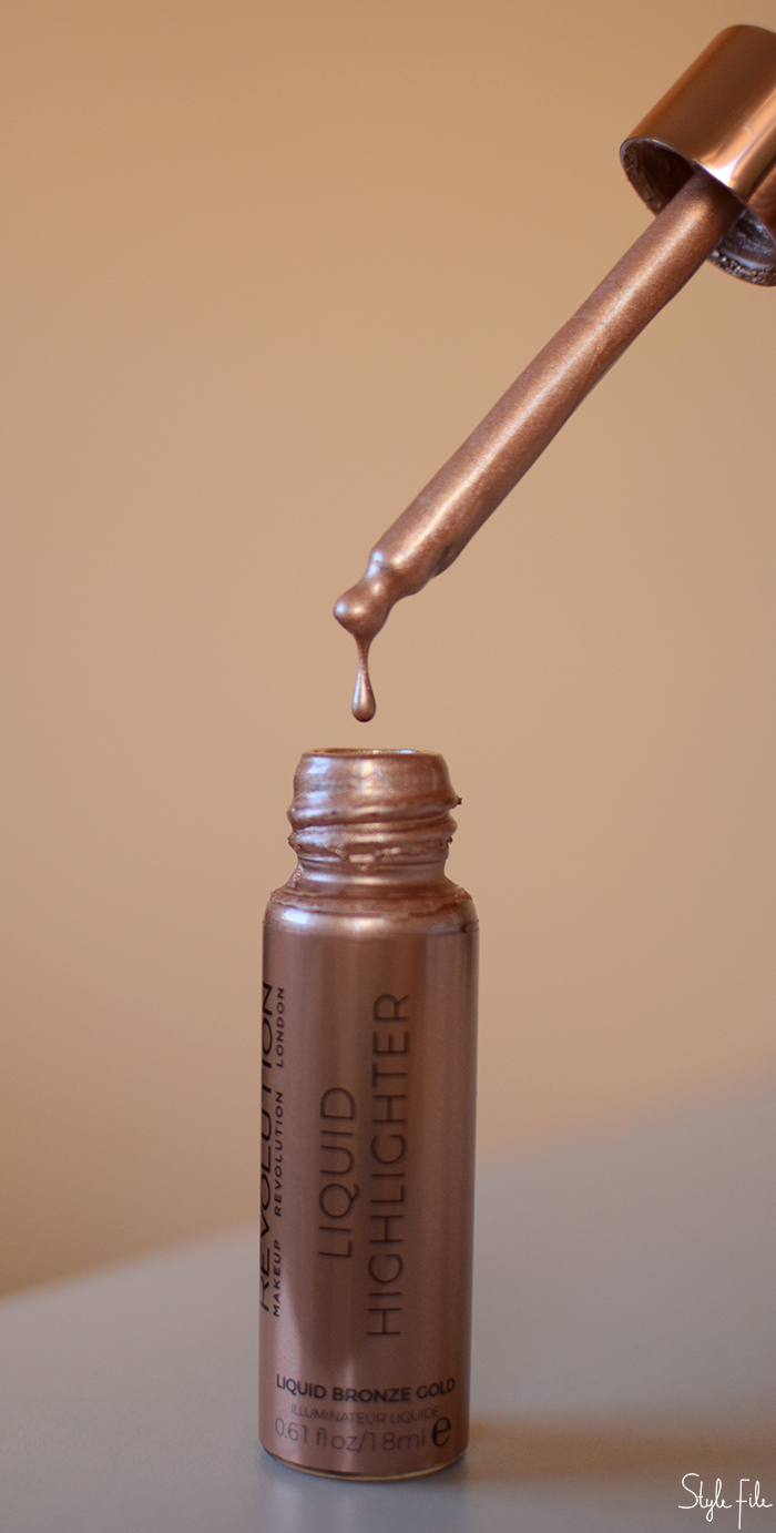 An image of Makeup Revolution liquid illuminator in a rose gold bottle with a dropper in front of a peach background for a beauty review