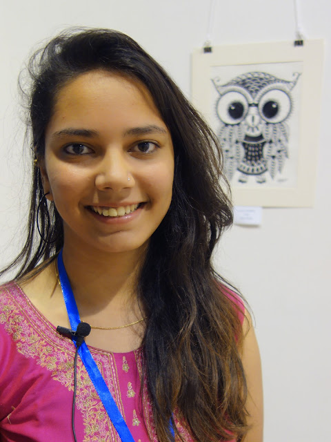 Antara Chowkase at Khula Aasmaan exhibition with her artwork in the background (www.indiaart.com)
