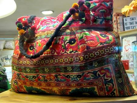 Bolso de tela bordada con flores en tonos rojos.
