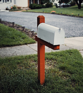 A white mailbox on a red wooden post next to a sidewalk and driveway.
