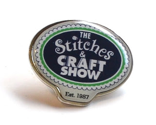 "An oval-shaped badge with a silver backing, white text on a dark blue oval bordered by a green line and white scallop shapes. The text reads ""The Stitches & Craft Show Est. 1987"""