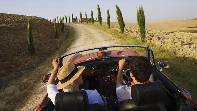 Homem e mulher em carro conversível