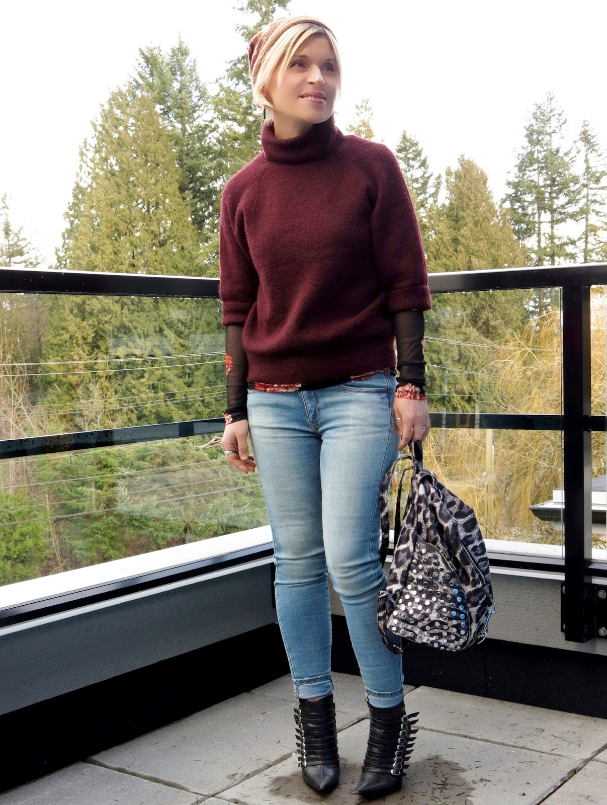 styling a sheer floral top under a chunky turtleneck, with skinny jeans, stiletto booties, and a beanie