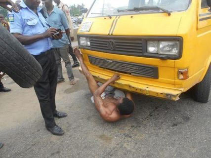 Lagos driver jumps under his bus to resist arrest, towing of vehicle