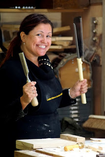 A smiling woman holding a saw and a chisel.