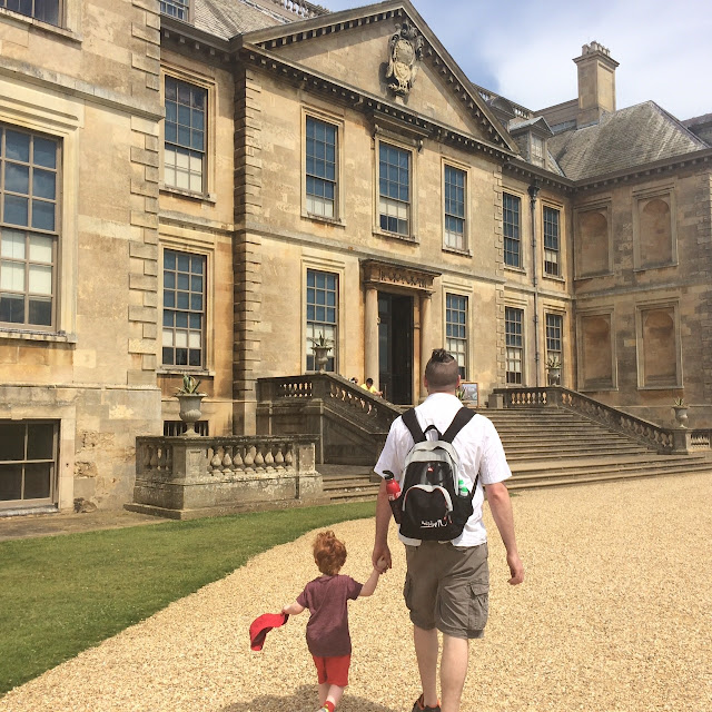 Dad and son walking towards a stately home
