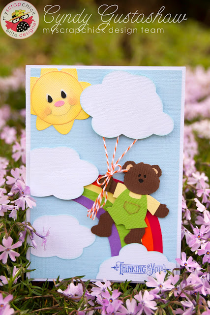 Handmade card of a bear floating over a rainbow with a cloud balloon