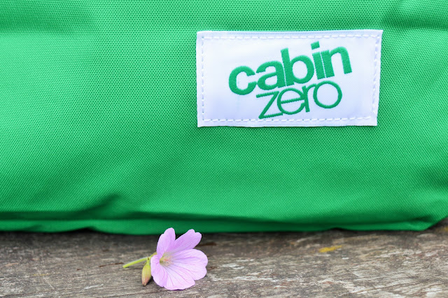Close up of green bag with 'cabin zero' and a flower in front.