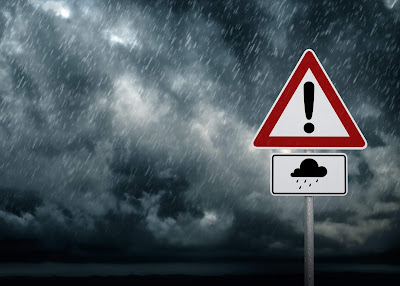 Image of a dark storm.  Road sign with an exclamation point and cloud icon.