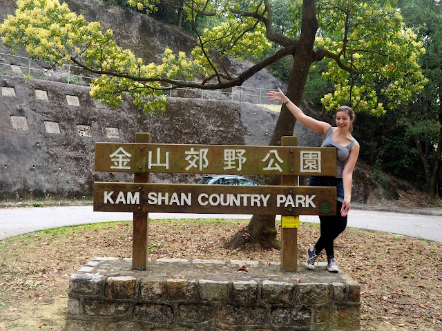 Girl posing with the Kam Shan Country Park sign, at the end of Monkey Mountain trail, near Tsuen Wan, New Territories, Hong Kong