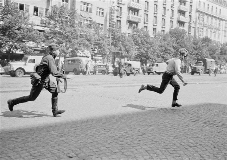 24 Rare Historical Photos That Will Leave You Speechless - During the Prague Spring in 1968, a Soviet soldier chases a young Czech man who was throwing rocks at a tank.