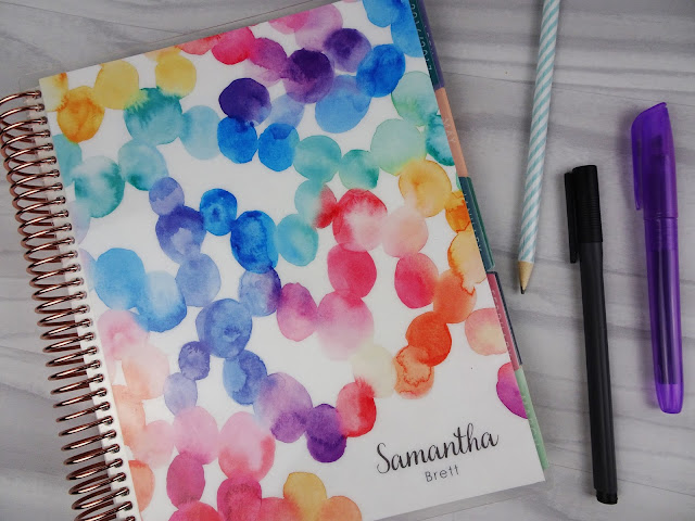 Erin Condren planner and pens on white wooden background