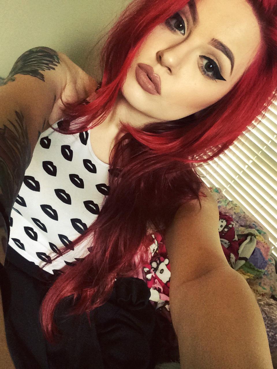 Foto de una chica de pelo rojo y labios rojos, lleva tatuajes de alas en los brazos