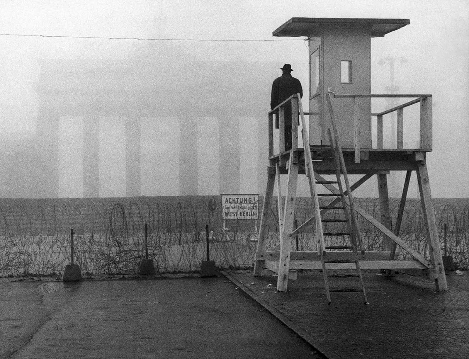 The Brandenburg Gate is shrouded in fog as a man looks from a watchtower over the Wall to the Eastern part of the divided city on November 25, 1961. The tower was erected by the West German police to observe the Inner-German border.