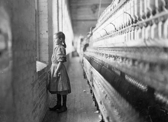A 10-year-old spinner at the Rhodes Mfg. Co. takes a momentary glimpse of the outside world. She said she had been working there for more than a year. Photographed in Lincolnton, North Carolina, in November of 1908.