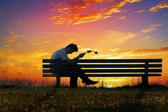 Hombre sentado en una banca sufriendo por desamor